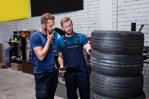 KFZ-Mechaniker weist Kunden auf Gefahren für Reifenschäden durch falsche Lagerung hin.